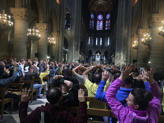 People inside Notre Dame cathedral sit with their hands in the air, after an attack on police in Paris. Picture: Nancy Soderberg via AP