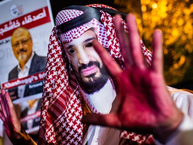 A protester wears a mask of depicting Saudi Crown Prince Mohammad Bin Salman with red painted hands next to people holding posters of Saudi journalist Jamal Khashoggi during the demonstration outside the Saudi Arabia consulate in Istanbul. Picture: AFP