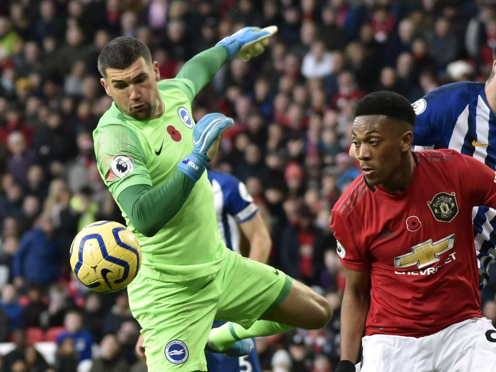 Brighton's goalkeeper Mathew Ryan, left, makes a save in front of Manchester United's Anthony Martial during the English Premier League soccer match between Manchester United and Brighton and Hove Albion, at the Old Trafford stadium in Manchester, England, Sunday, Nov. 10, 2019. (AP Photo/Rui Vieira)