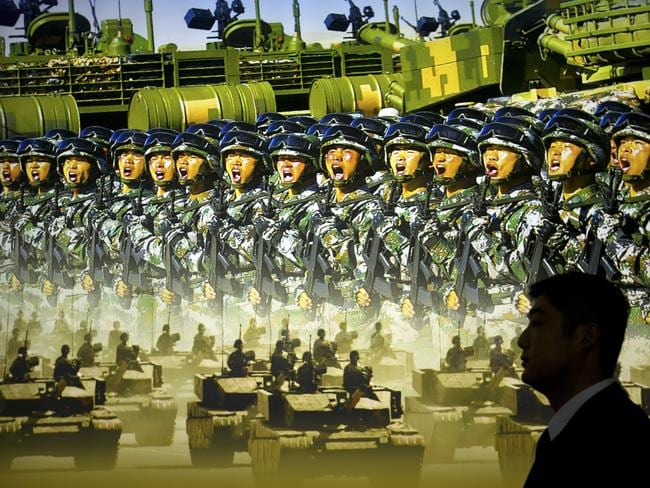 A man walks past a mural showing Chinese soldiers and military hardware at an exhibition highlighting China's achievements under five years of leadership of Xi Jinping.
