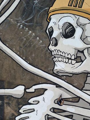 A person walks across Bennett's large skeleton mural. Picture: Kitt Bennett