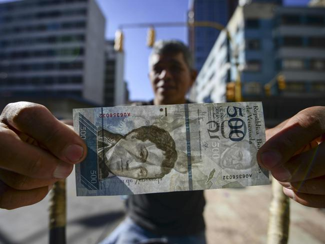 A street coffee vendor shows a new 500-Bolivar-note (74 cents of US dollar) in Caracas on January 16, 2017. The new 500-Bolivar-note is the first of a new family of currency that will progressively come into circulation. The South American country also has the highest inflation rate in the world, which IMF forecasts say could soon hit 475 percent. / AFP PHOTO / JUAN BARRETO