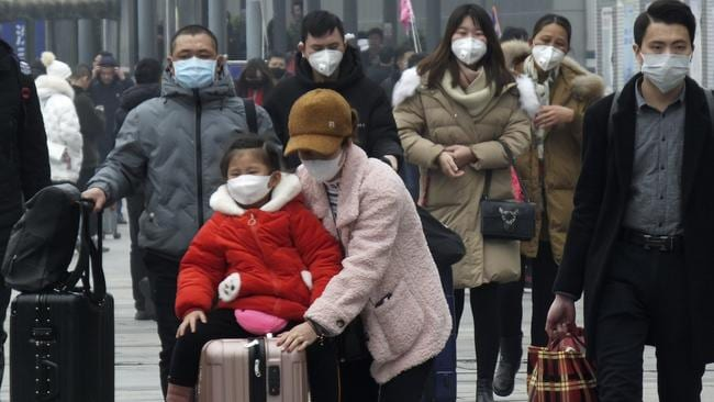 Travellers wear masks at Yichang train station, west of Wuhan, on Wednesday. Picture: AP
