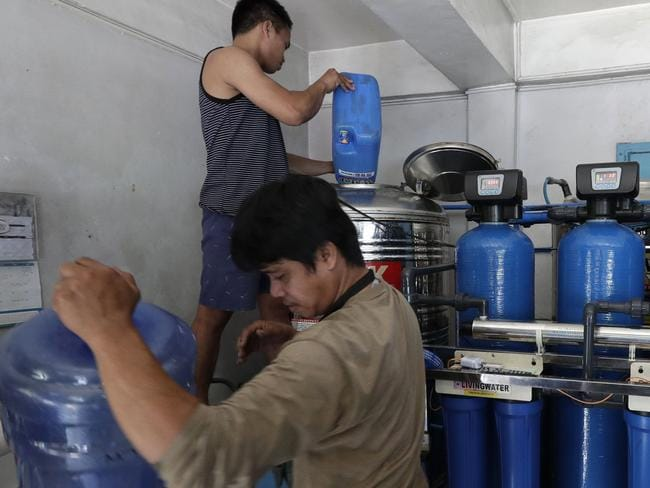 Workers prepare to filter water at a purifying station while they wait for the water supply to return at their area in Mandaluyong, metropolitan Manila, Philippines. Picture: AP