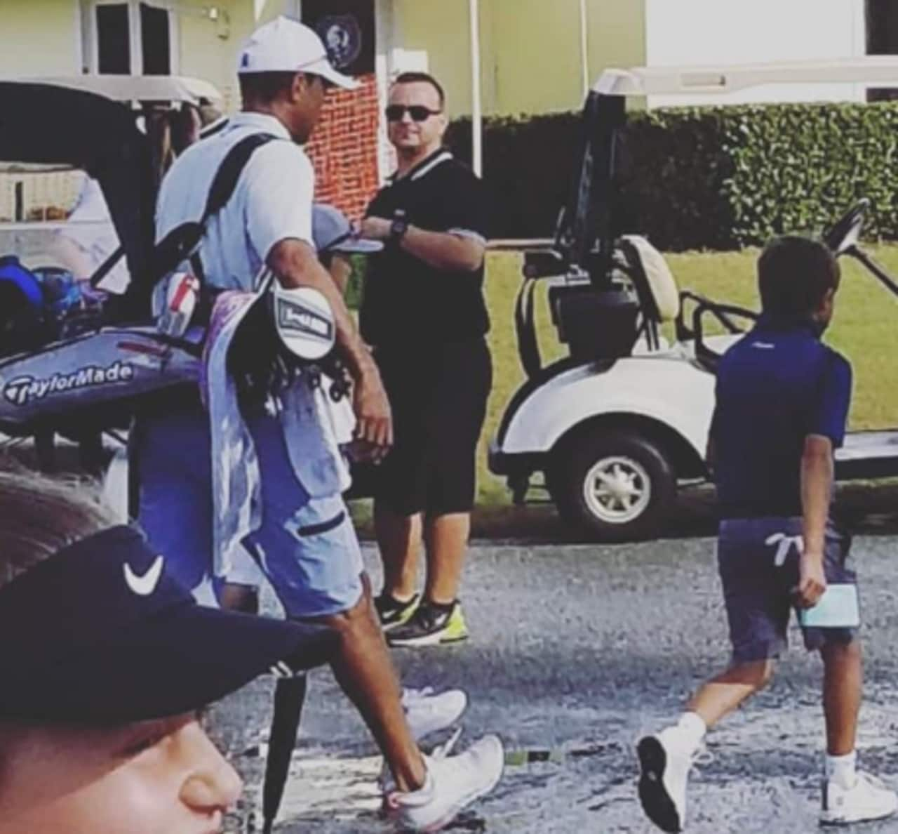 Tiger carries the bag for his son Charlie.