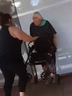 The elderly woman tries to shield herself.