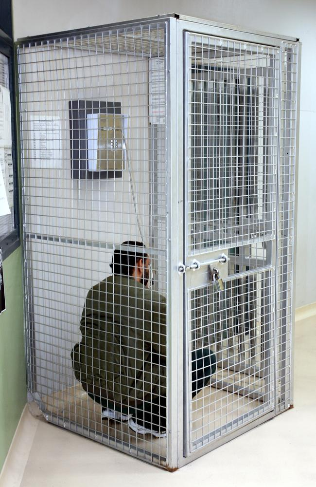 A high-risk prisoner sits locked inside a cage as he talks on a phone in Goulburn's Supermax.  <br />