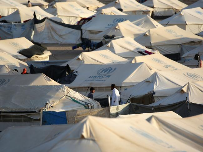 Men stand in between UNHCR tents at a refugee camp housing Iraqi families who fled fighting in the Mosul area in the northeastern town of al-Hol in Syria's Hasakeh province. Picture: Delil Souleiman.