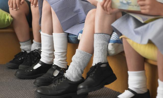Low section of elementary students sitting in row in classroom