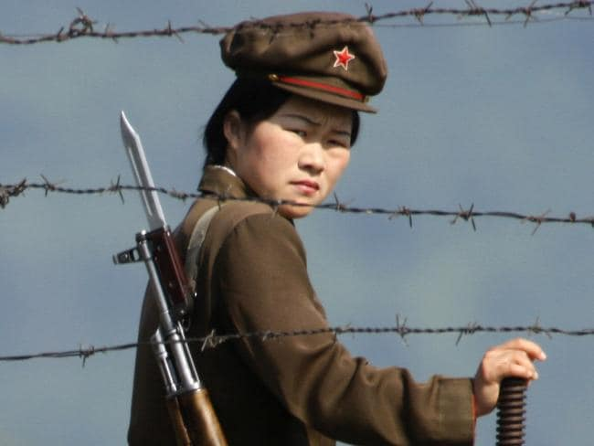 A female North Korean soldier looks out from behind a barbed wire fence around a camp on the North Korean river banks across from Hekou, northeastern China's Liaoning province. Picture: Ng Han Guan/AP