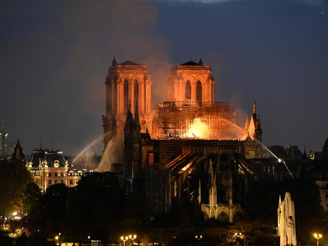 Firefighters douse flames rising from the roof at Notre Dame Cathedral in Paris. Picture: AFP