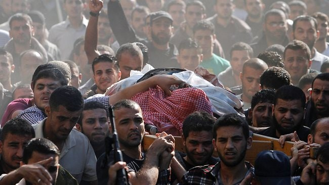 Palestinian mourners carry the body of Hamas' top military commander Ahmed Jabari, who was killed in an Israeli strike on Wednesday, during his funeral in Gaza City yesterday. The assault killed 10 other Palestinians, including two children and seven militants. Picture: Getty Images