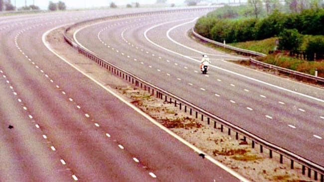 A lone police motorcyclist travels along the normally packed M6 motorway in central England in April 1997 after parts of the motorway were closed due to a terror alert.