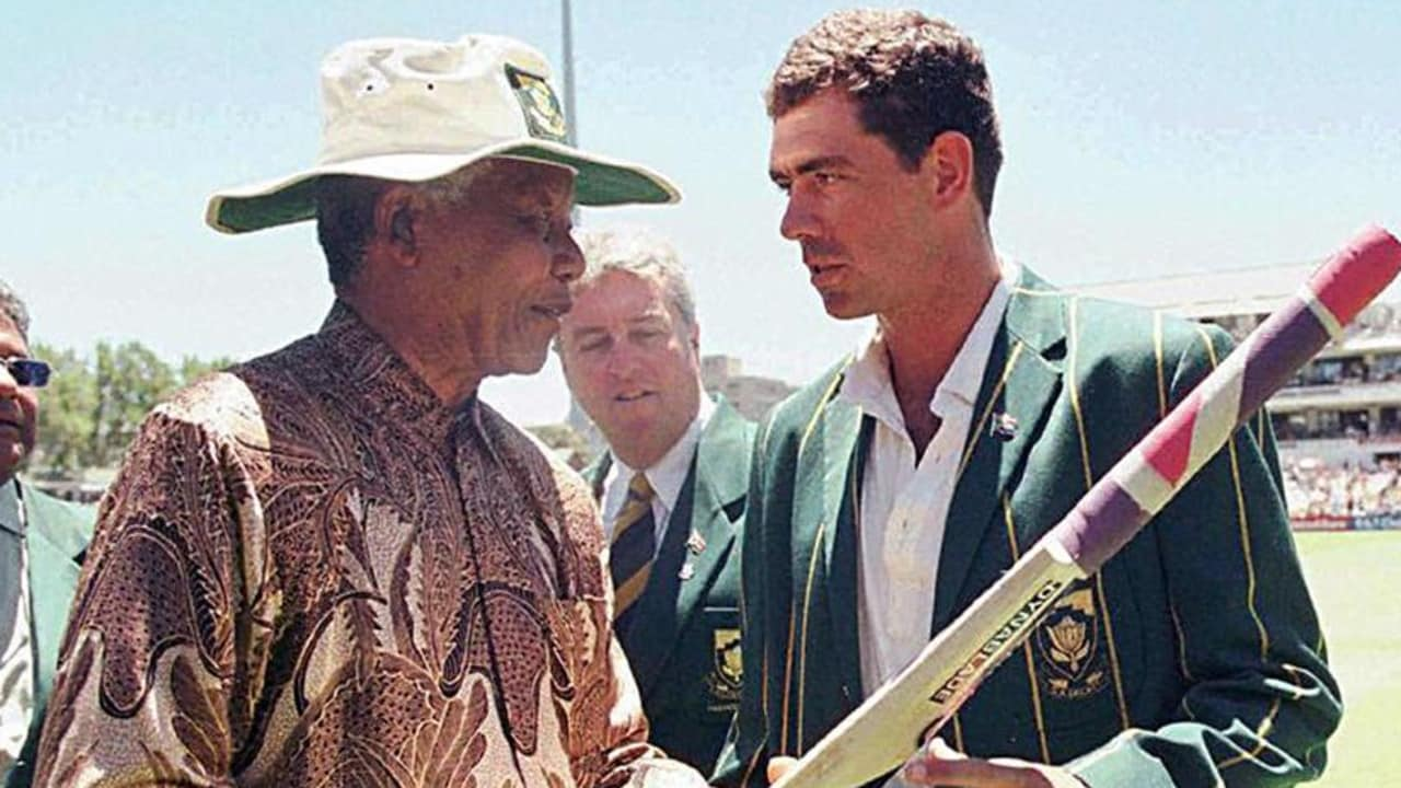 South African President Nelson Mandela receives a cricket bat from the South African Cricket captain, Hansie Cronje, during the lunch break on the third day of the Second Test between South Africa and India at Newlands on January 4, 1997. AFP PHOTO / POOL - ADIL BRADLOW