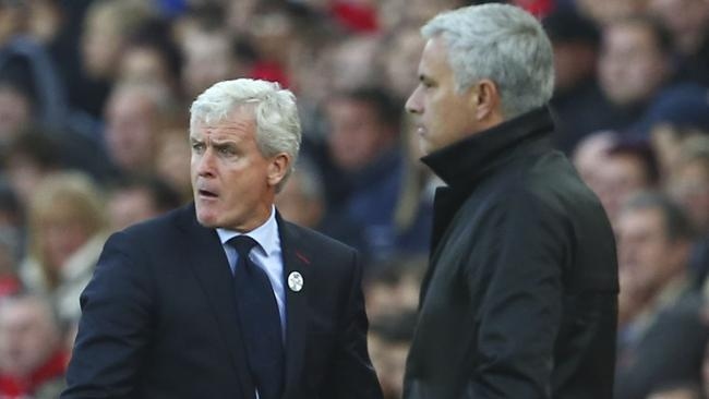 Stoke City's Welsh manager Mark Hughes (L) and Manchester United's Portuguese manager Jose Mourinho (R)
