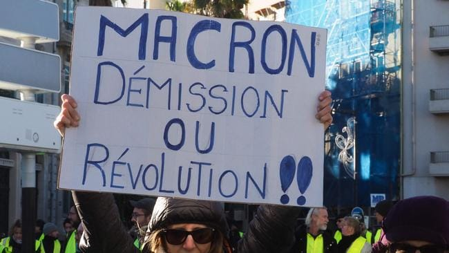 "A protester holds up a placard reading in French ""Macron, resignation or revolution"". Picture: AFP"