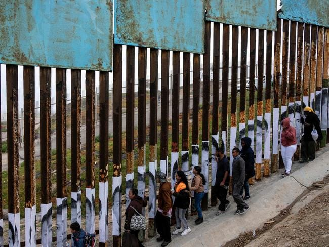 "Central American migrants travelling in the ""Migrant Via Crucis"" caravan demonstrate at the US/Mexico border. Picture: AFP Photo"