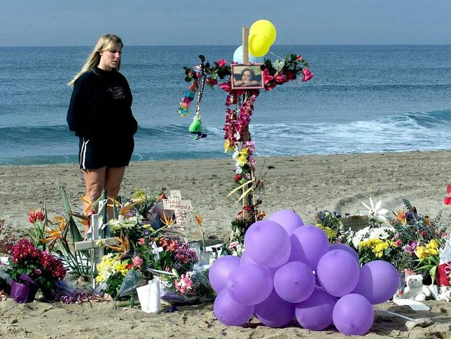 A woman stands by one of several makeshift memorials set up along the coastline in Oxnard, California, following the crash of Alaska Airlines flight 261.