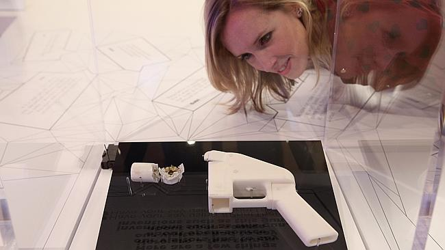 A woman admires a 3D printed handgun which was created and fired by Finnish journalist Ville Vaarne. (Photo by Oli Scarff/Getty Images)