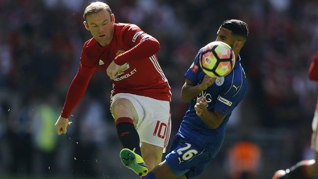 Manchester United's Wayne Rooney (L) and Leicester's Riyad Mahrez challenge for the ball.