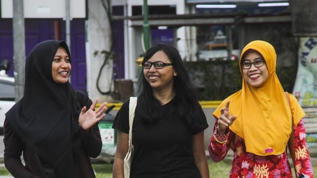 Sri Mulyana, centre, with friends in Batang, where she wears a jilbab to work as a condition of her employment but otherwise chooses not to wear the headscarf, and for this she endures criticism. Picture: Budi Purwanto