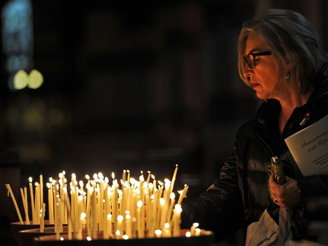 World grieves ... A woman lights a candle at a multi-faith service for victims of MH17 at St. Paul's Cathedral in Melbourne on July 24. Picture: AFP