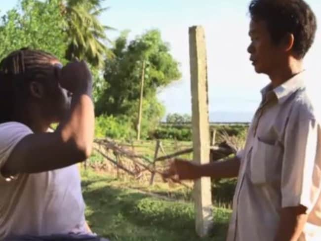 Pham Van Minh, who believes dioxin levels are putting his family at risk, shows presenter Ade Adepitan where his crops fail to grow.