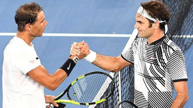 Still brothers, gracious stars Roger Federer and Rafael Nadal meet in the middle of Rod Laver Arena. Picture: AAP