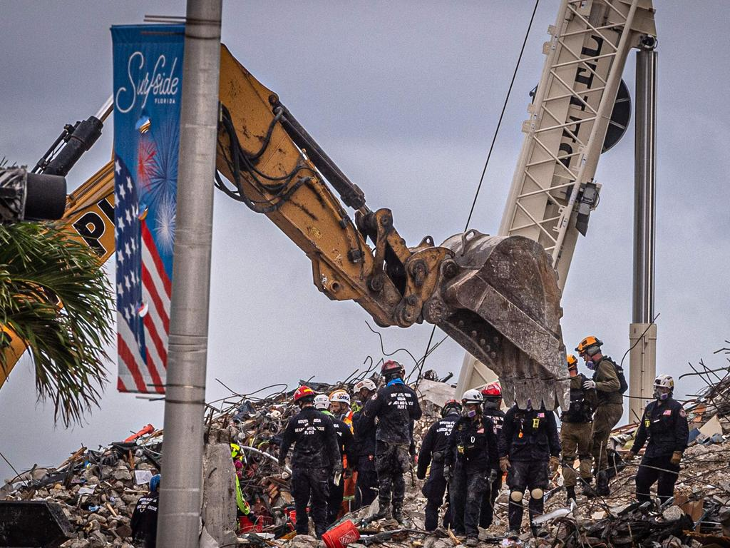 Search and rescue teams look for possible survivors in the rubble of the partially collapsed 12-story Champlain Towers South building can be seen in Surfside, Florida.