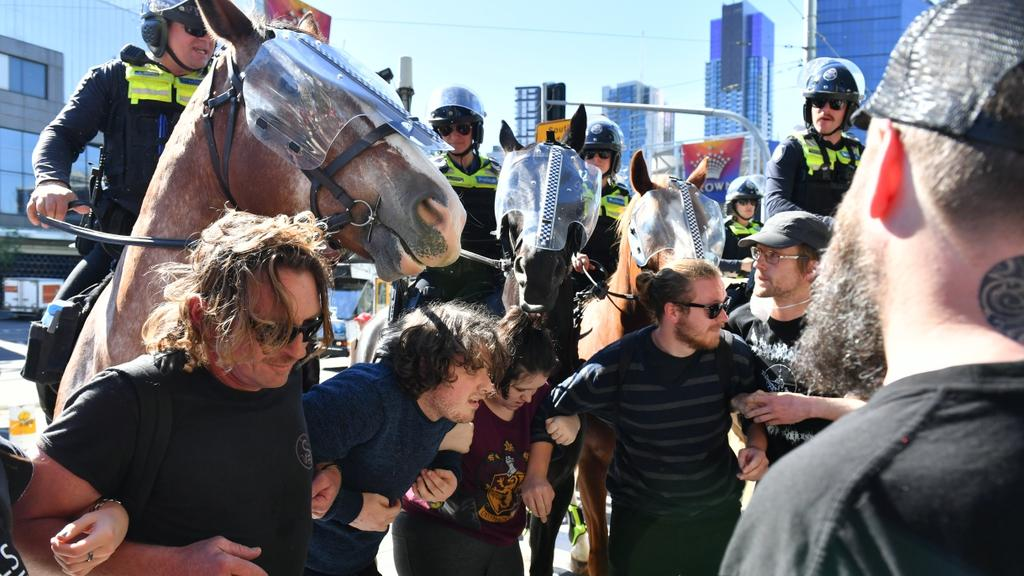Police horses move in a group of protesters. Picture: Jake Nowakowski