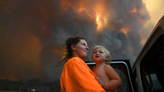 Sharnie More and her daughter Charlotte look on as thick smoke rises from bushfires near Nana Glen. Picture: AAP
