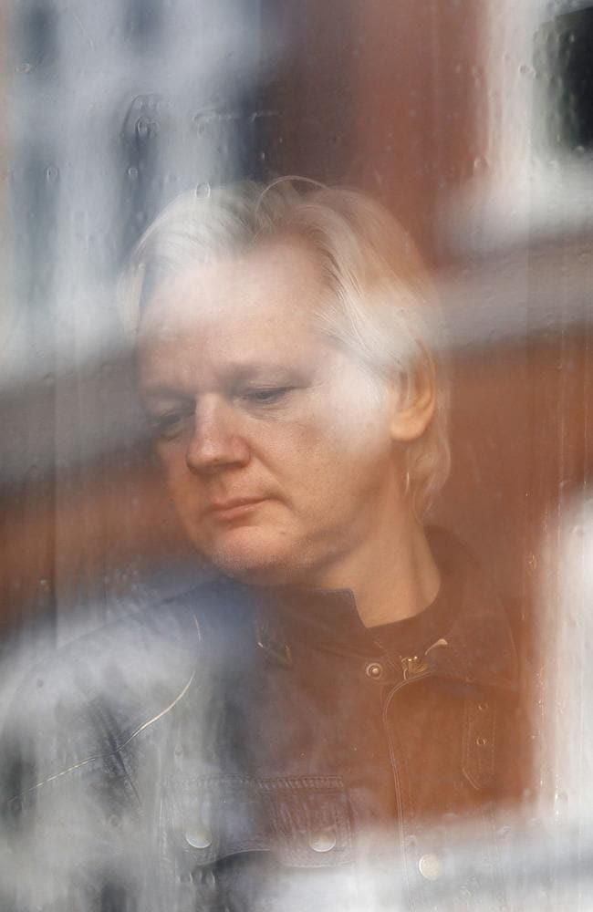 Julian Assange, pictured in the window of the Ecuadorean Embassy in London where he has taken political asylum since 2012. Picture: AP/Frank Augstein