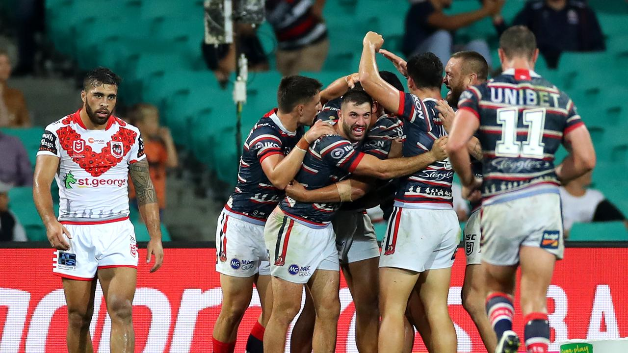 Roosters celebrate Sio Siua Taukeiaho's match-sealing try against Dragons.