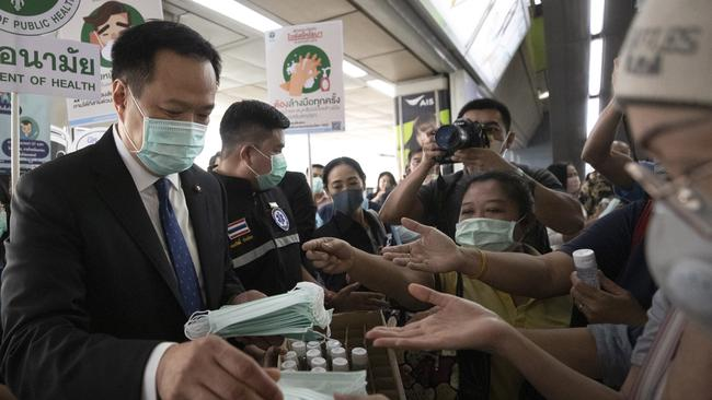 Thailand's Public Health Minister Anutin Charnvirakul (left) distributes masks to commuters during a campaign for wearing masks and washing hands at the skytrain station in Bangkok, Thailand. Picture: AP/Sakchai Lalit