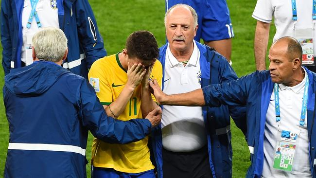 Scolari of Brazil and staff console Oscar after a 7-1 defeat to Germany.