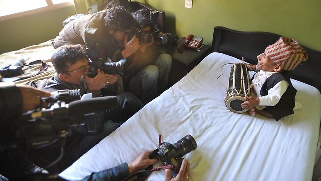Chandra Bahadur Dangi plays a drum for photographers in Kathmandu, where he was staying to be measured for a world record. Picture: AFP