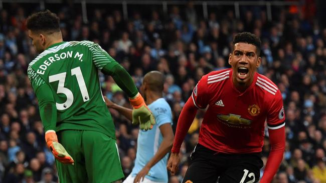 Manchester United's English defender Chris Smalling (R) celebrates scoring his team's third goal