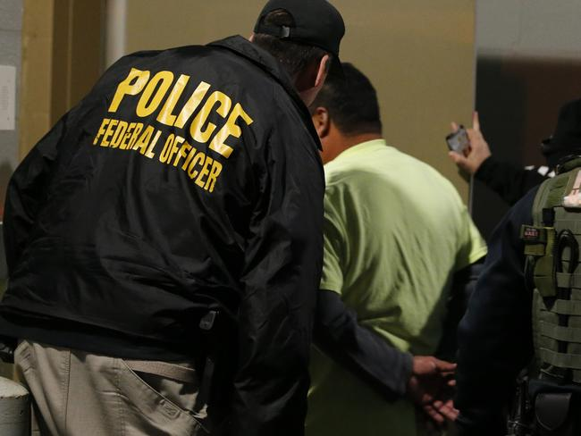 US Immigration and Customs Enforcement agents escort a target to lockup during a raid in Richmond, Virginia. Picture: AP