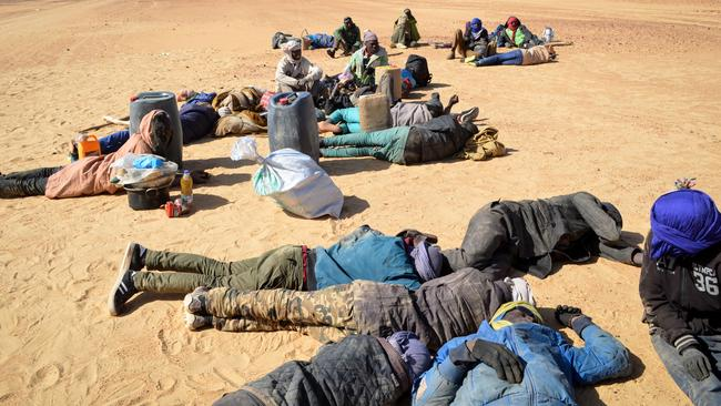 A group of migrant men, mainly from Niger and Nigeria, have a rest before carrying on with their journey across the Air dessert towards the Libyan border post of Gatrone. Picture: Soulemaine Ag Anara