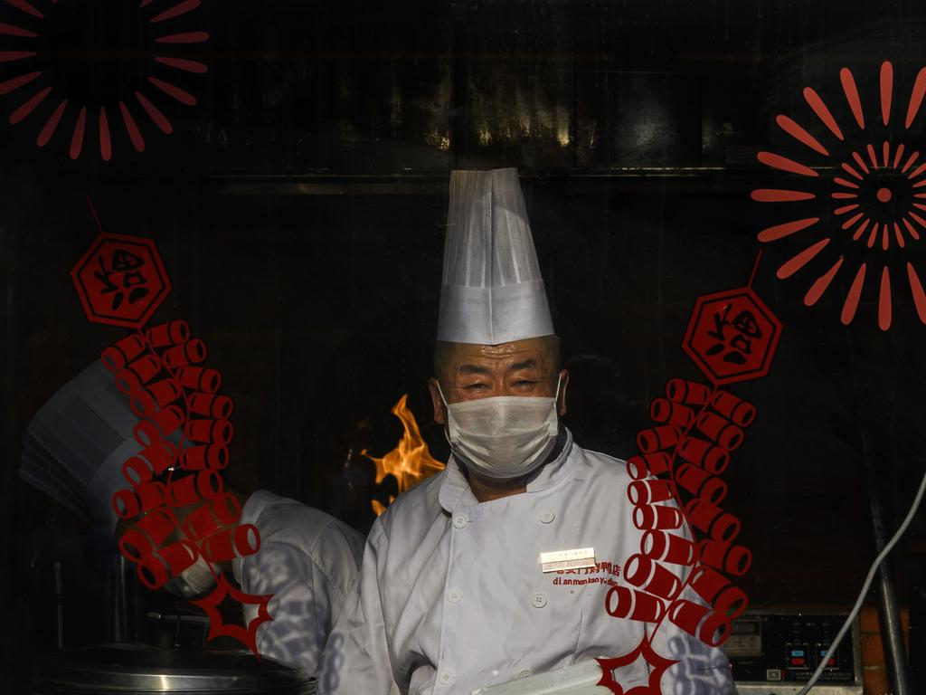 A chef in Beijing wears a protective mask as he works in a restaurant. Picture: Getty Images