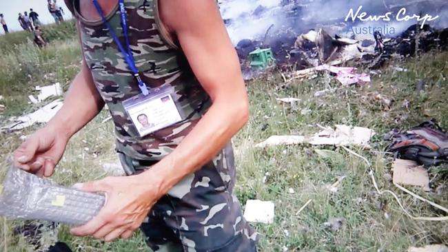 Utter lack of respect ... Militia going through passengers bags and personal belongings just after MH17 crashed. Picture: Supplied
