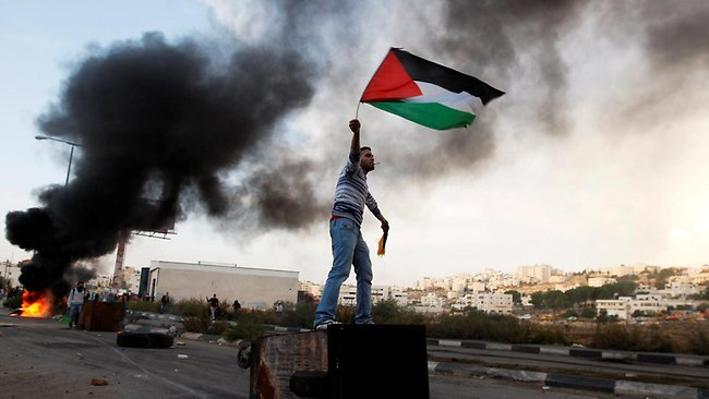 A man waves the Palestinian flag during a protest against Israel's operations in Gaza Strip, outside Ofer, an Israeli military prison near the West Bank city of Ramallah. Picture: Majdi Mohammed