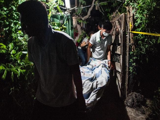 Forensic officers remove the body of an alleged drug dealer in Manila. Picture: Getty Images
