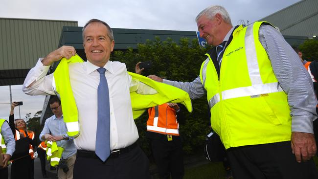 Bill Shorten puts on a high visibility vest during a visit to the Sydney Markets in Sydney. Picture: AAP