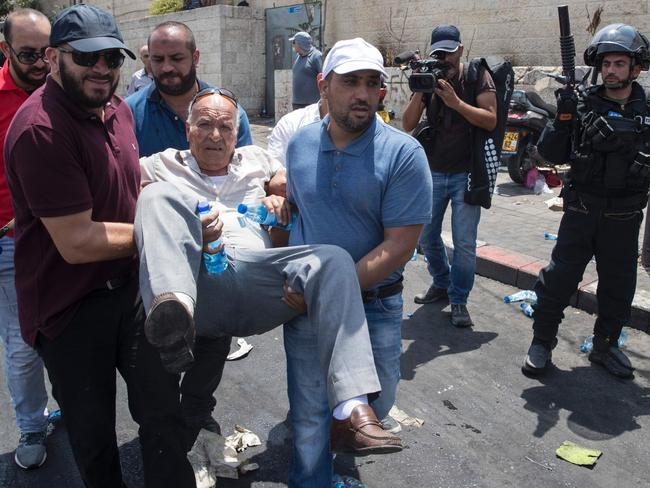 Palestinians carry a wounded man during clashes with Israeli security forces outside Jerusalem's Old City in front of the Al-Aqsa mosque compound. Picture: AFP