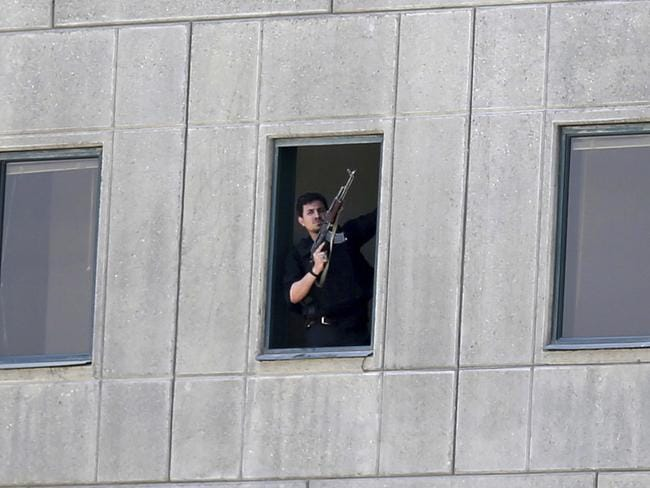 An armed man stands in a window of the parliament building in Tehran, Iran. Several attackers stormed into Iran's parliament and a suicide bomber targeted the shrine of Ayatollah Ruhollah Khomeini. Picture: Fars News Agency, Omid Vahabzadeh via AP