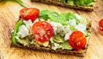 Healthy Snack from Wholegrain Rye Crispbread Crackers with Avocado, Cherry Tomatoes, Rocket Salad and Goat Cheese