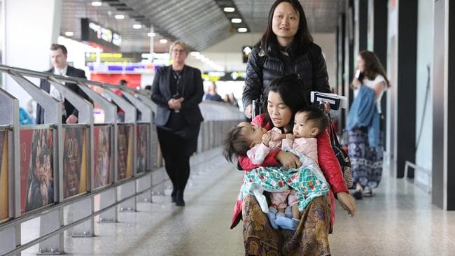 Travelling nurse Tshewang Choden pushes mum Bhumchu Zangmo in a wheelchair as she holds Nima and Dawa arriving into Melbourne. Picture: Alex Coppel