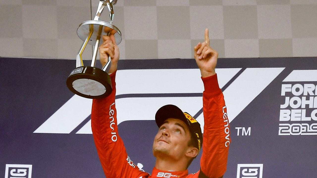 Winner Ferrari's Monegasque driver Charles Leclerc holds his trophy and gestures towards the sky in tribute to late French driver Anthoine Hubert.