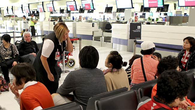 A Qantas employee at Sydney airport tries to explain the situation to would-be passengers / Picture: Rohan Kelly